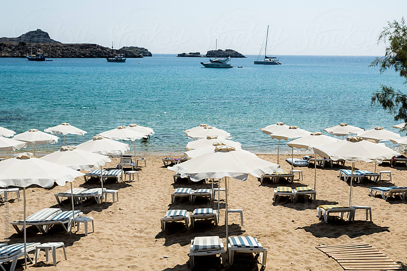 Sunbeds sea and parasols  Lindos bay by Paul Phillips for Stocksy United