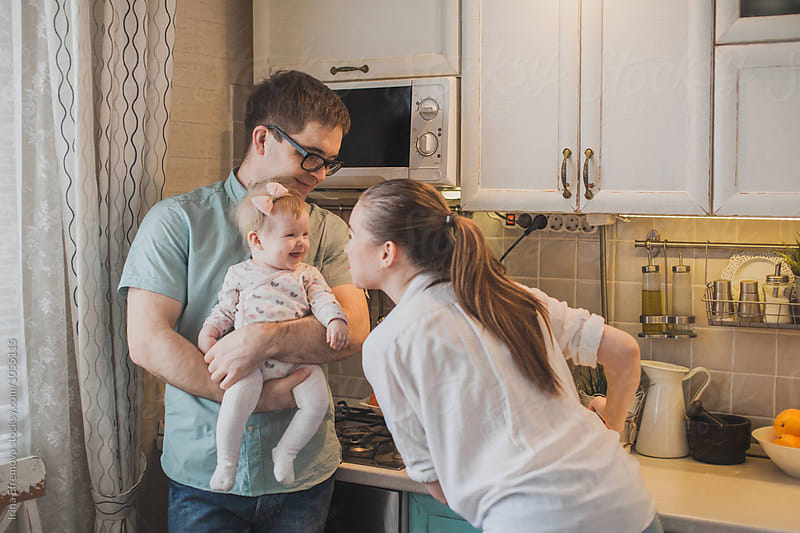 Mother and father on a tiny kitchen with their baby daughter  by Irina Efremova for Stocksy United