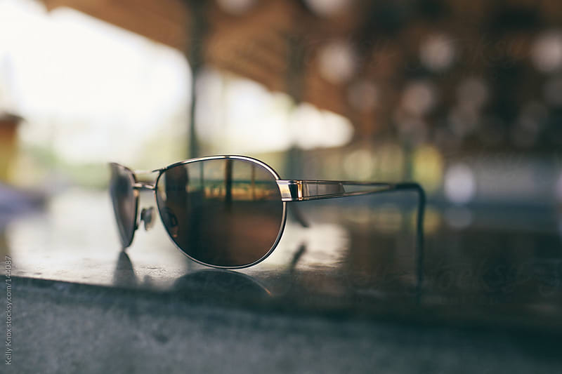 sunglasses on a beach bar by Kelly Knox for Stocksy United