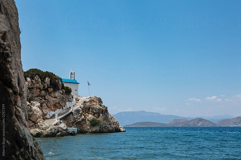 Greek church on rocky island by Alberto Bogo for Stocksy United