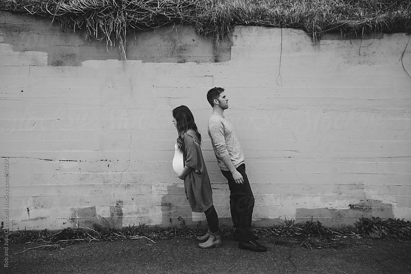 Pregnant couple leaning awkwardly by cement wall by Rob and Julia Campbell for Stocksy United