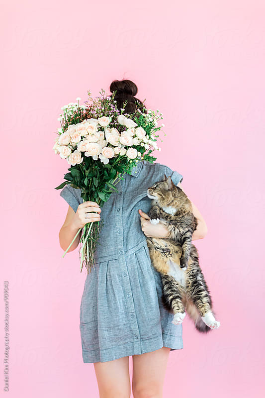 Woman holding flowers and cat by Daniel Kim Photography for Stocksy United