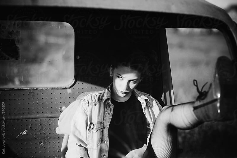 Black and white photo of a girl in car by Koki Jovanovic for Stocksy United
