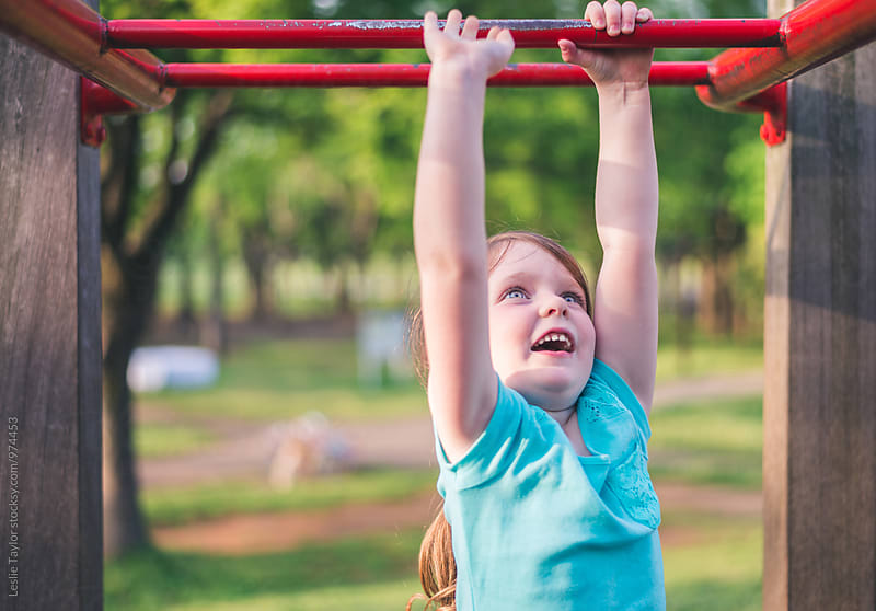 Girl Playing On Monkey Bars With A Smile by Leslie Taylor for Stocksy United