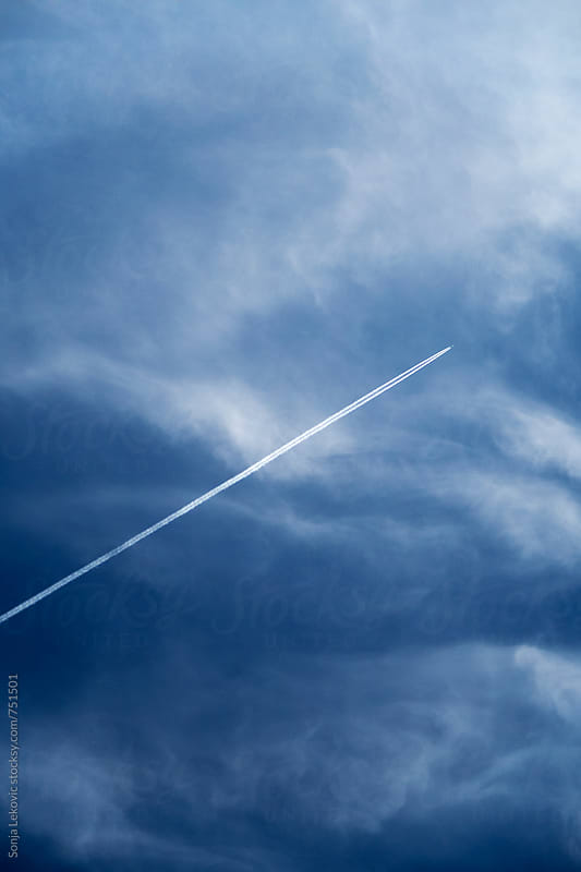 blue sky and airplane trail by Sonja Lekovic for Stocksy United