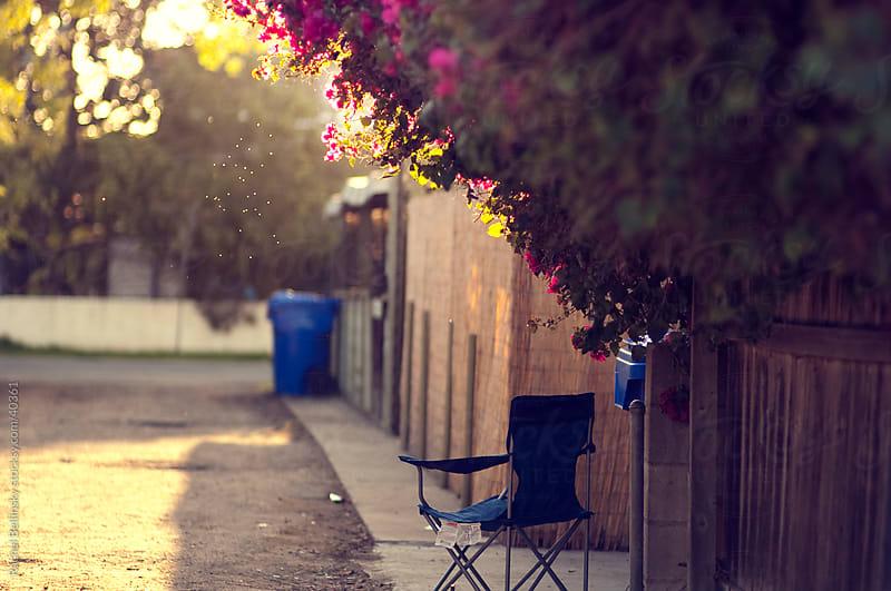 Blue folding chair in sunny alley by Rachel Bellinsky for Stocksy United