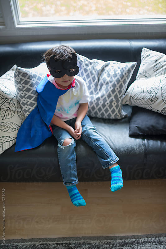 young child in home made cape and mask waits patiently by Tara Romasanta for Stocksy United