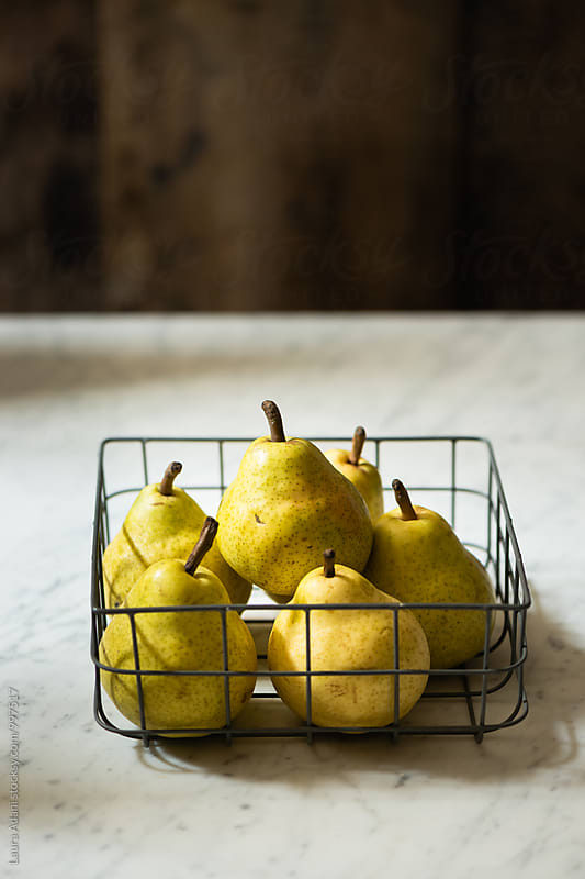 Fresh pears in a metal basket on a table by Laura Adani for Stocksy United