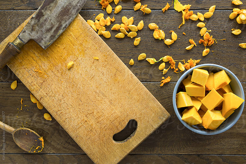 Chopped orange pumpkin with seeds scattered on table, overhread by Kirsty Begg for Stocksy United
