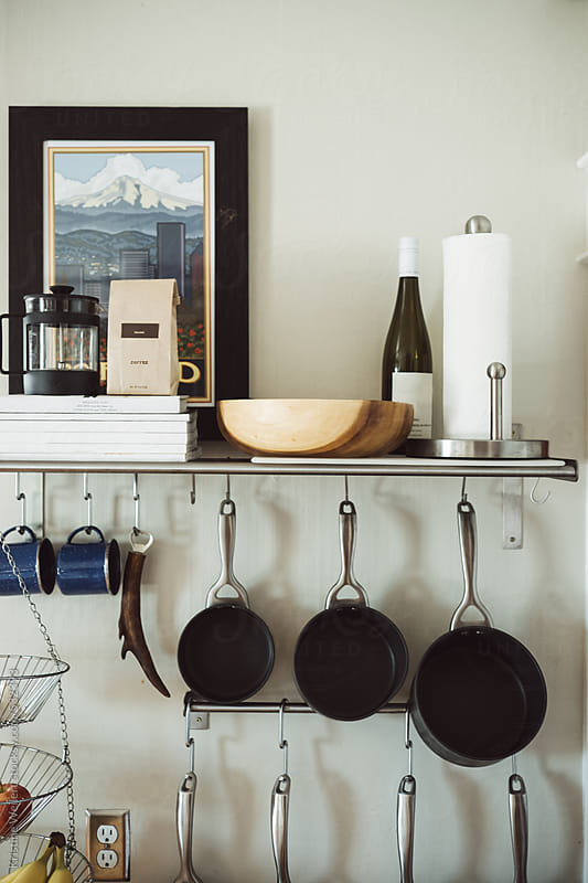 Kitchen pots and pans and other utensils organized and hanging on a wall  by Kristine Weilert for Stocksy United