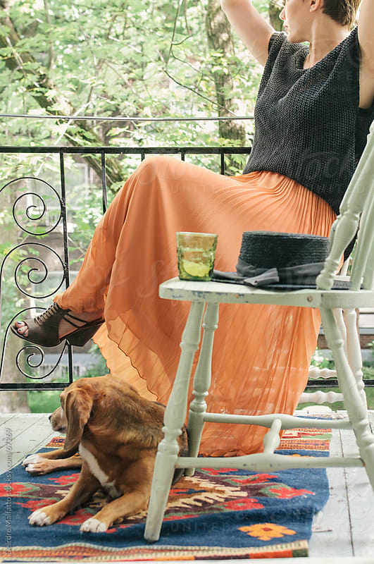 woman and her dog relax on a balcony by Deirdre Malfatto for Stocksy United