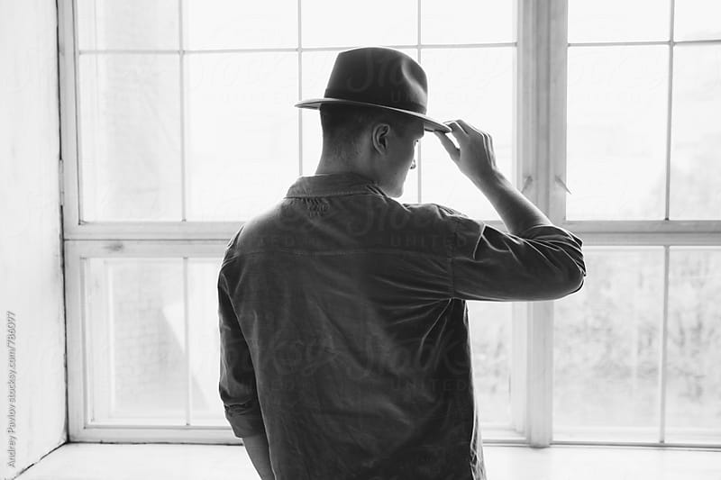 Man holding his hat in front of big window by Andrey Pavlov for Stocksy United