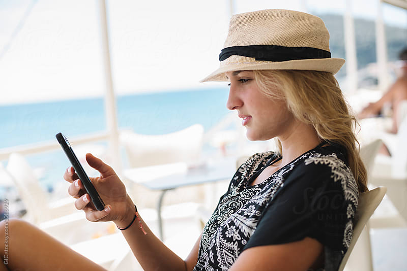 Young blonde woman using a phone at the beach by GIC for Stocksy United