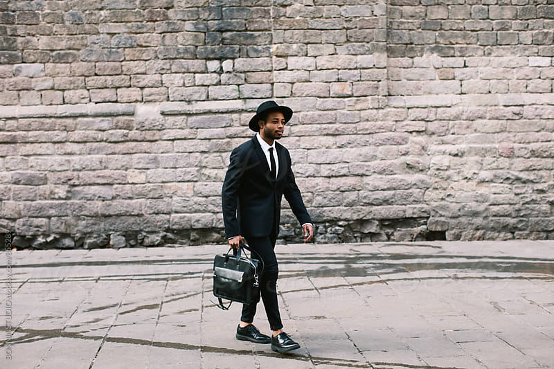 Stylish businessman holding his briefcase walking on the street. by BONNINSTUDIO for Stocksy United