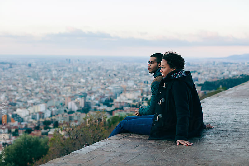 Side view of couple sitting above city at sunrise. by BONNINSTUDIO for Stocksy United