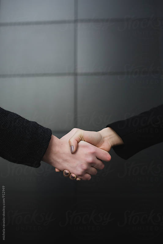 Handshake between man and woman by michela ravasio for Stocksy United