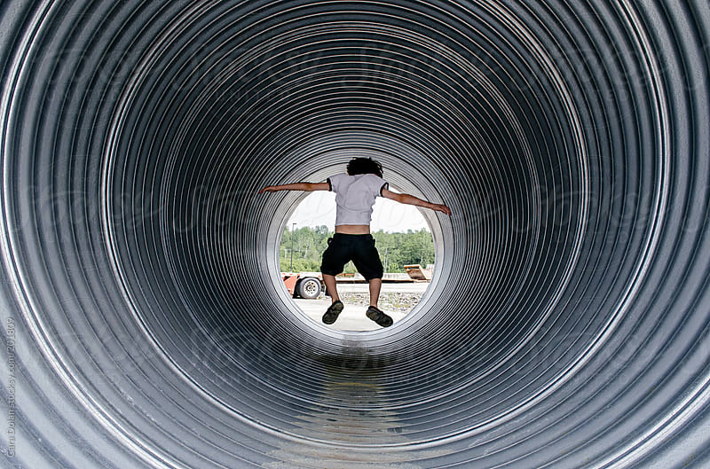 Child plays inside a large industrial pipe by Cara Dolan for Stocksy United