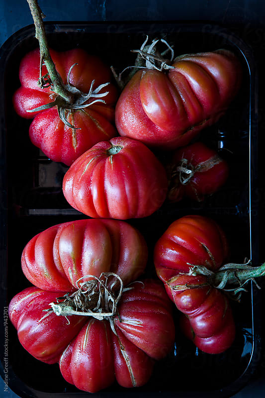 Red heirloom tomatoes from the farmers market by Nadine Greeff for Stocksy United