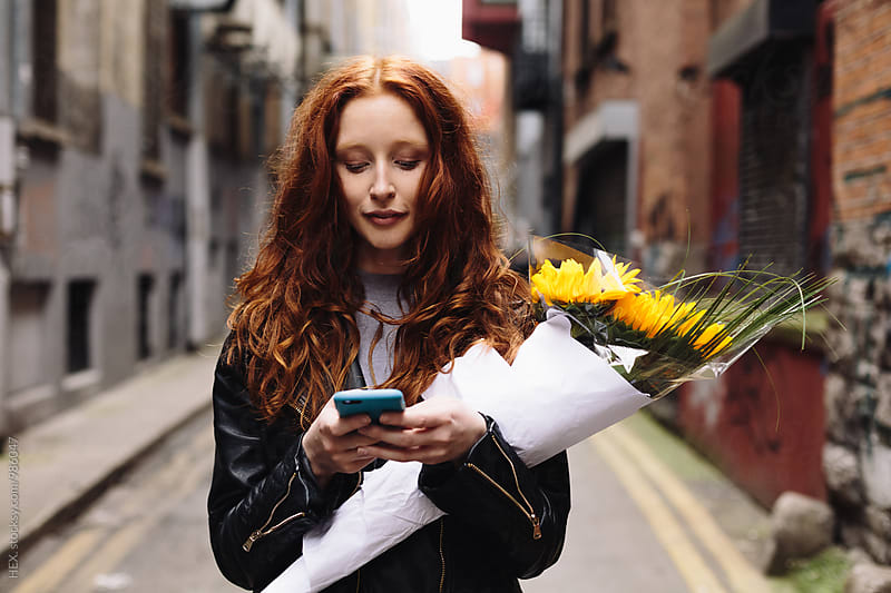 Young Woman Texting a message on the Mobile Phone by HEX. for Stocksy United