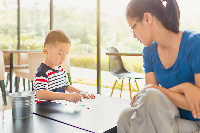 Kid drawing on paper with crayon on table and mother watching by Lawren Lu for Stocksy United