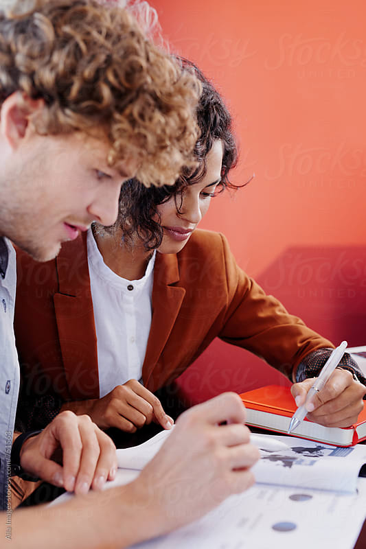 Two Business people working with documents by Aila Images for Stocksy United