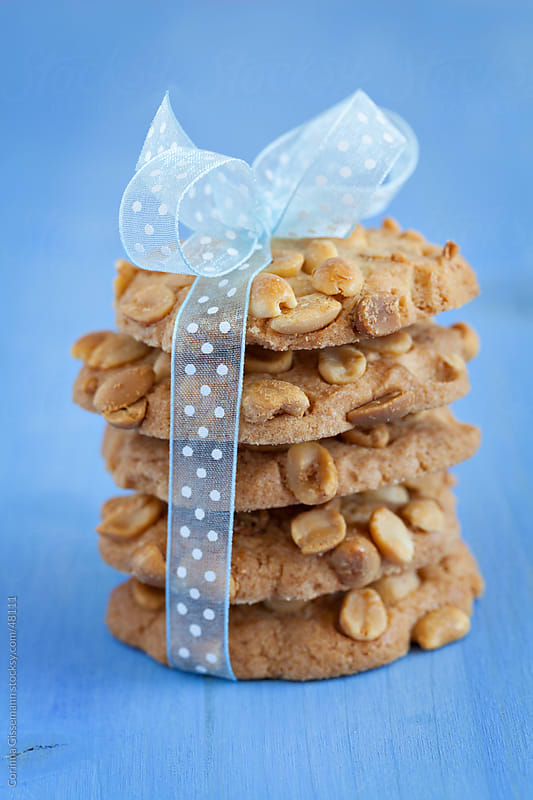 a stack of baked peanut cookies with a bow on blue background by Corinna Gissemann for Stocksy United