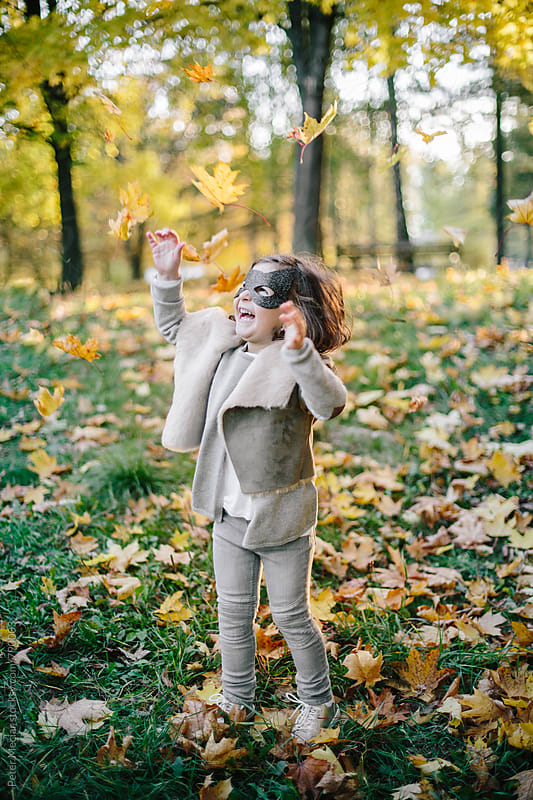 Little girl with a face mask is playing in autumn park and throw autumn leaves by Peter Meciar for Stocksy United