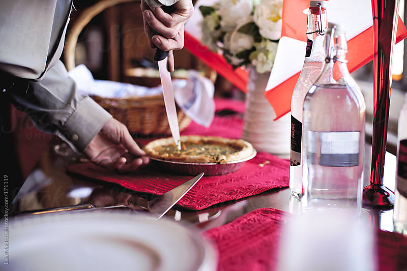 man cutting quiche on table with red and white accessories  by Lisa MacIntosh for Stocksy United