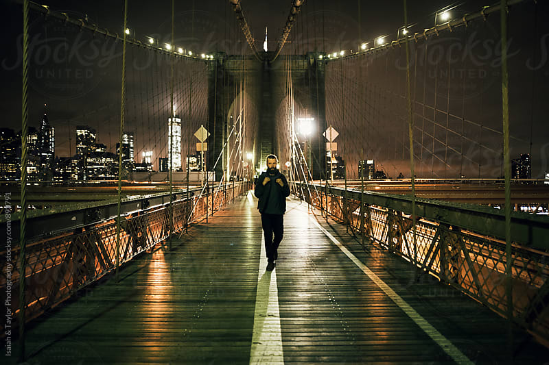 Man walking on bridge by Isaiah & Taylor Photography for Stocksy United