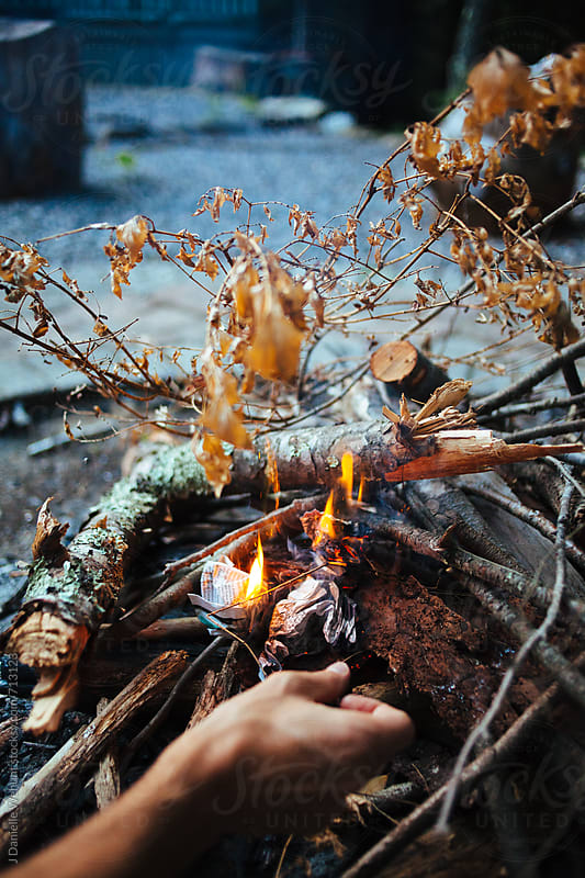 A caucasian man hand starting a fire with sticks and kindling.  by J Danielle Wehunt for Stocksy United
