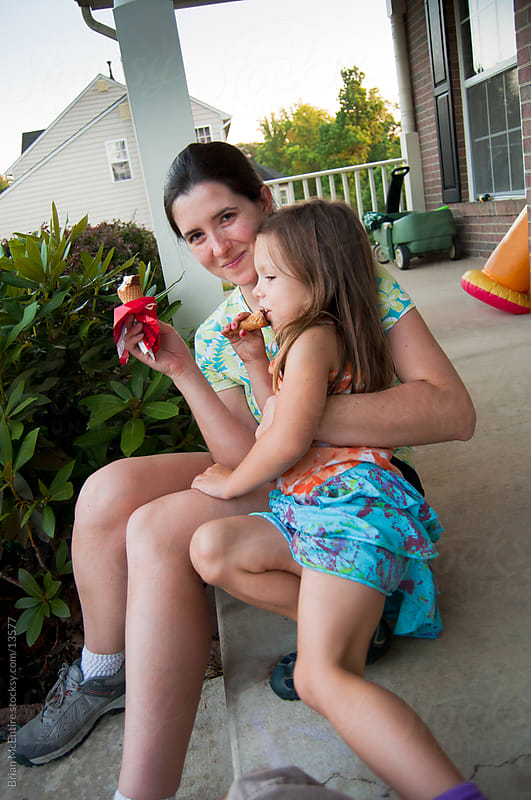 Summer Evening: Mother and Daughter Have Ice Cream on Porch by Brian McEntire for Stocksy United