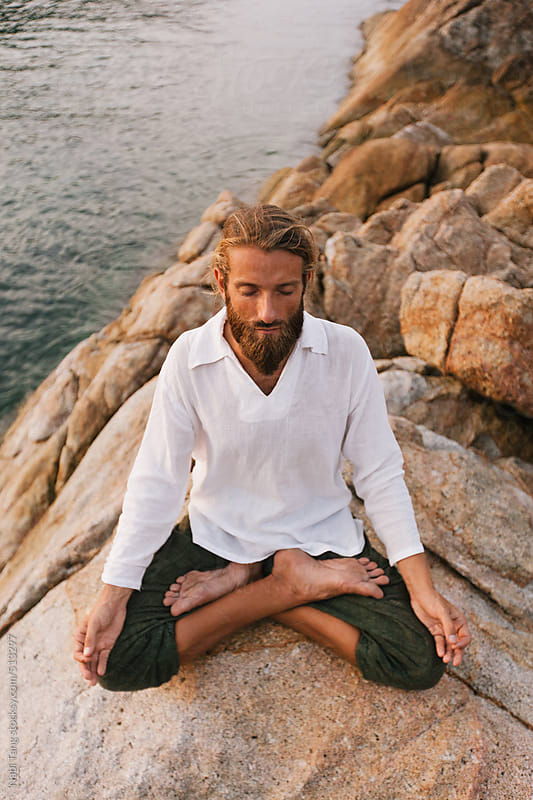 Young man meditating on the rock above the ocean by Nabi Tang for Stocksy United
