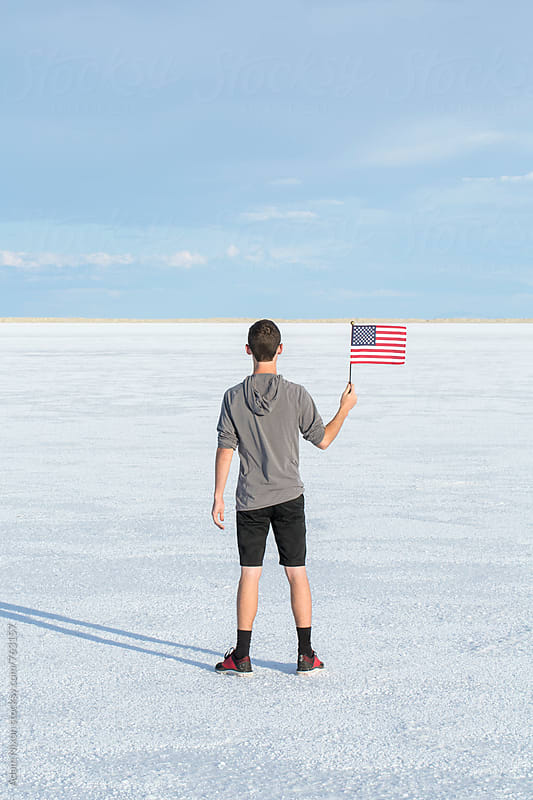 Portrait of young male waving an american flag in the salt flats of Utah by Adam Nixon for Stocksy United