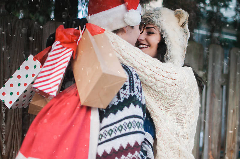 A young couple holding Christmas presents by Chelsea Victoria for Stocksy United