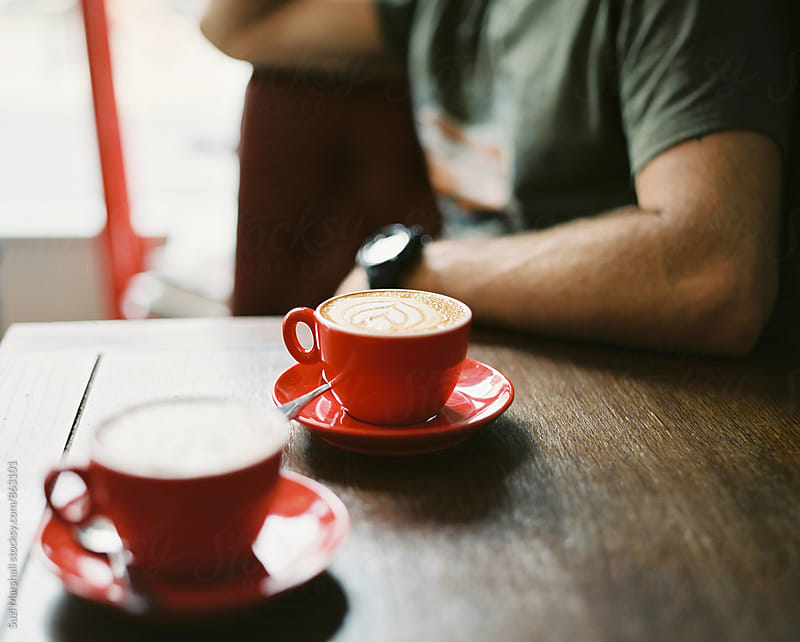 Two cups of coffee on a wooden table in a cafe with a man in the background by Suzi Marshall for Stocksy United