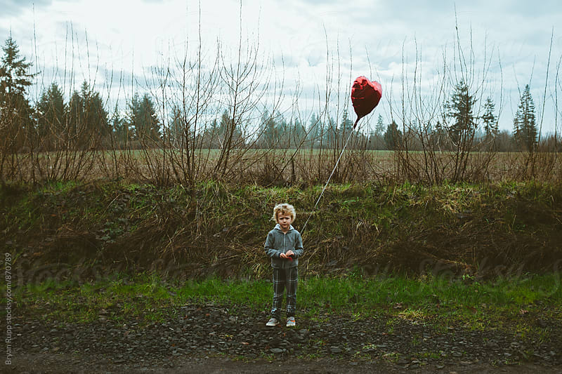 Little Boy Holding Balloon in a Field by Bryan Rupp for Stocksy United