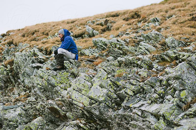 Young hiker sitting on the rocks by Marko Milovanović for Stocksy United