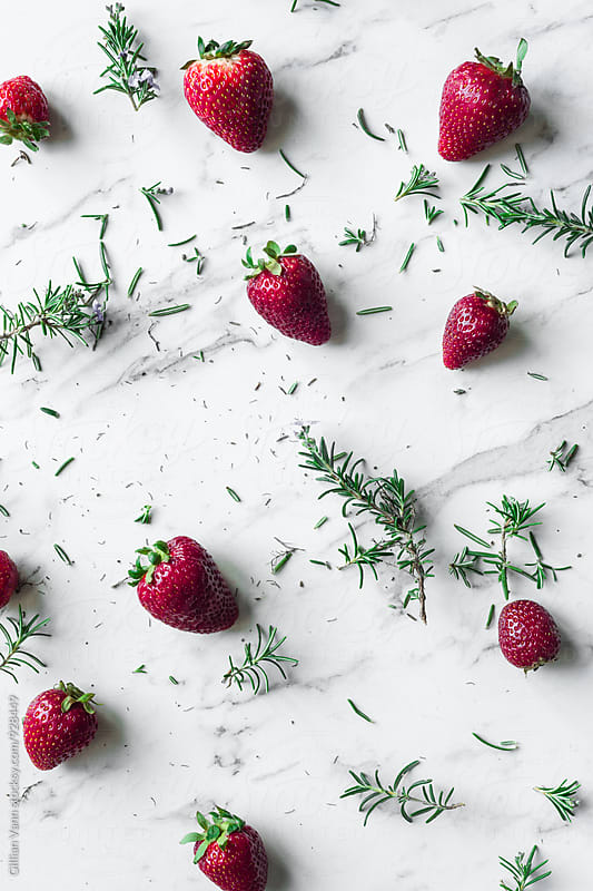 strawberries and rosemary sprigs on a marble background by Gillian Vann for Stocksy United