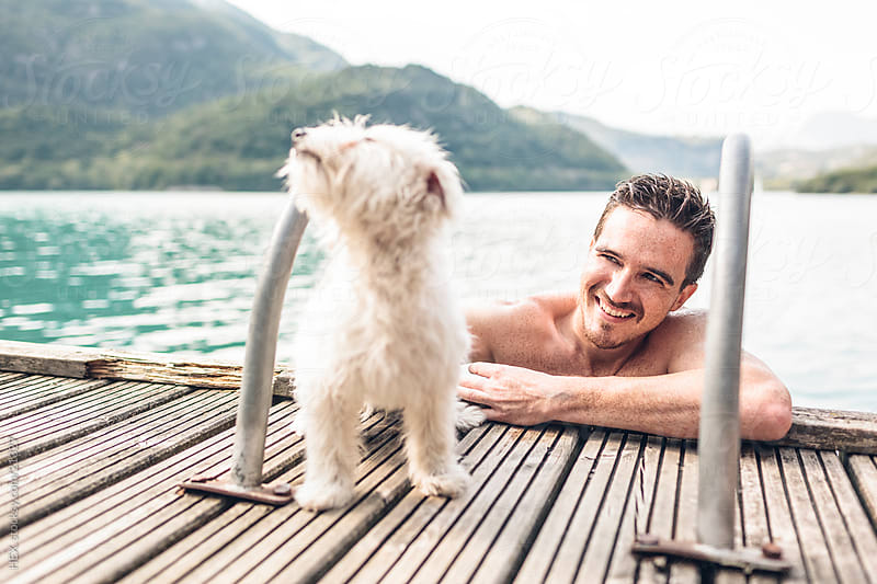 Smiling Man with Dog. Summer by HEX . for Stocksy United
