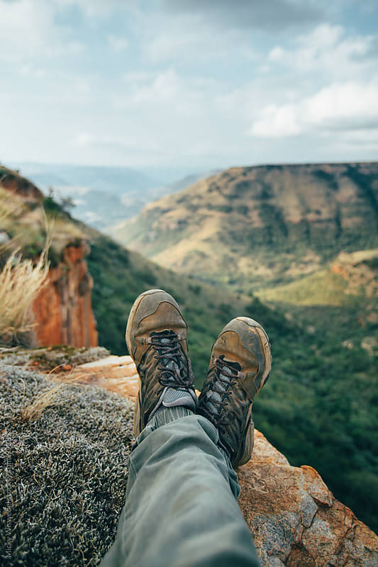 Point of view of a hiker with dirty trail shoes overlooking a scenic mountain valley by Micky Wiswedel for Stocksy United