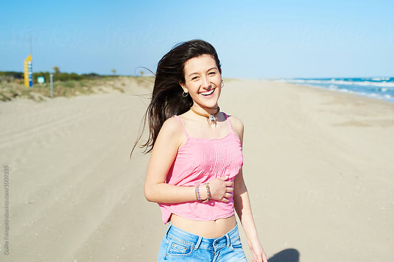Beautiful smiling young woman on beach by Guille Faingold for Stocksy United