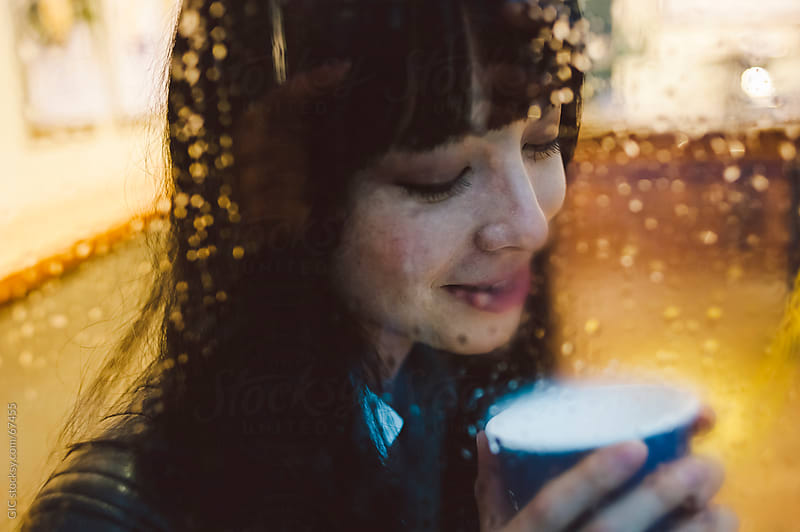 Woman drinking tea during a rainy day by Simone Becchetti for Stocksy United