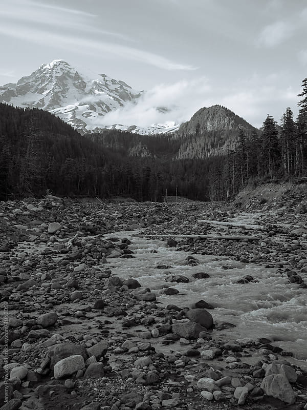 Black and white snow covered Mt. Rainier with glacial water rushing  by Jeremy Pawlowski for Stocksy United