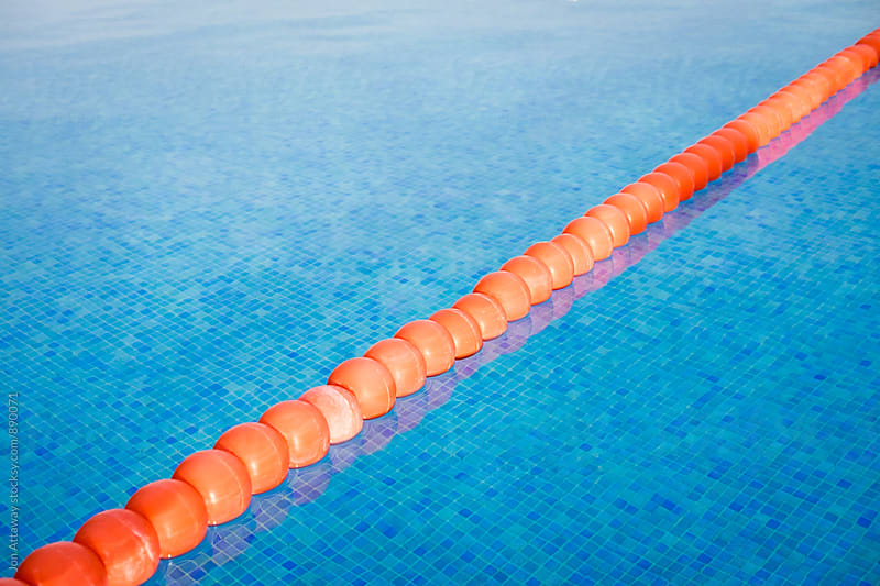 Bright orange safety floats on a bright blue swimming pool by Jon Attaway for Stocksy United