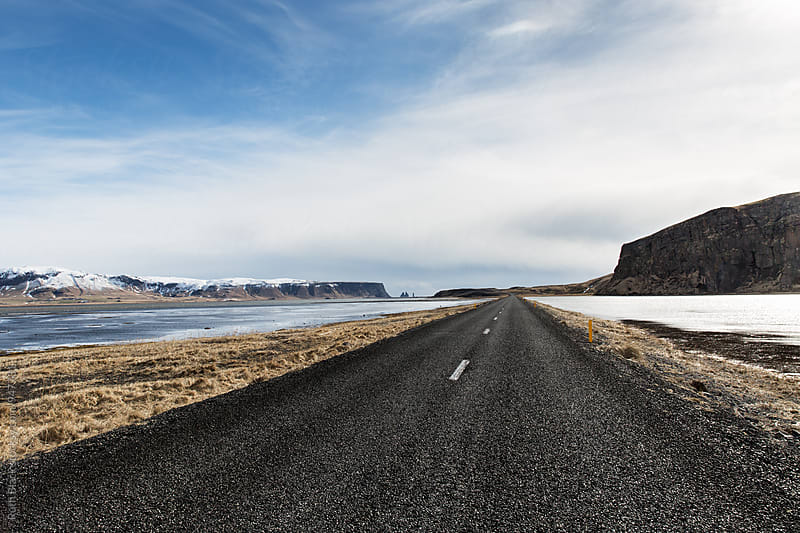 Icelandic road with Reynisdrangar sea stacks in the distance by Ruth Black for Stocksy United