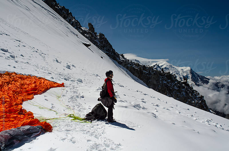young woman getting ready to paraglide from a glacier in the French alps by Neil Warburton for Stocksy United
