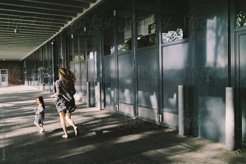 Mother and daughter running away through the sunbeam along the street by Evgenij Yulkin for Stocksy United