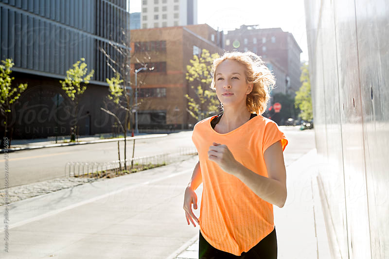 Woman running in a city by Ann-Sophie Fjelloe-Jensen for Stocksy United