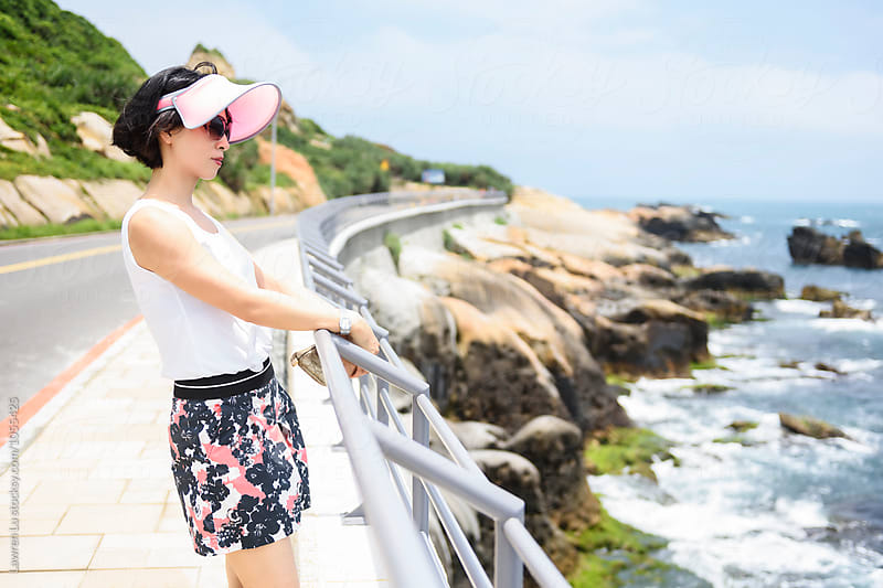 Side view of adult female tourist at railings watching sea by Lawren Lu for Stocksy United