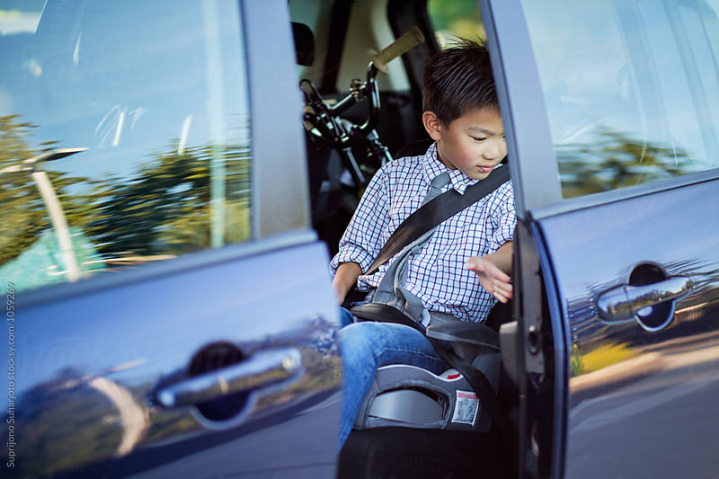 Back to school: Asian boy wearing a seat belt in a car by Suprijono Suharjoto for Stocksy United